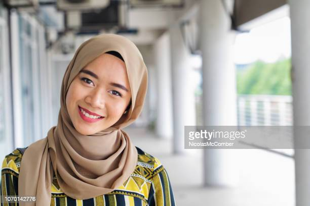 beautiful young muslim asian female smiling urban portrait - malaysian culture stock pictures, royalty-free photos & images