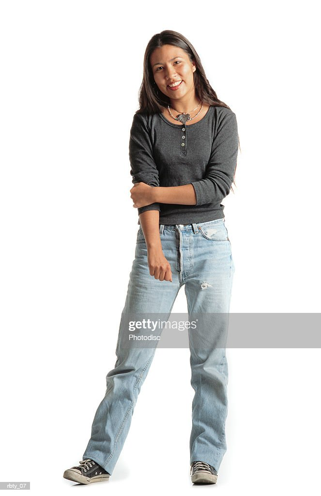 beautiful young native american woman dressed in gray shirt and blue jeans holds her arm while smiling into the camera : Foto de stock