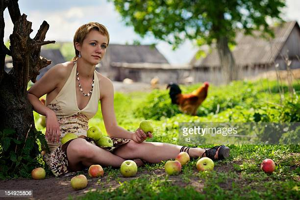Beautiful young peasant girl sitting near a tree with apples