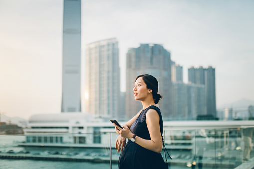 Beautiful young pregnant woman relaxing on balcony using smartphone, standing against urban cityscape - gettyimageskorea