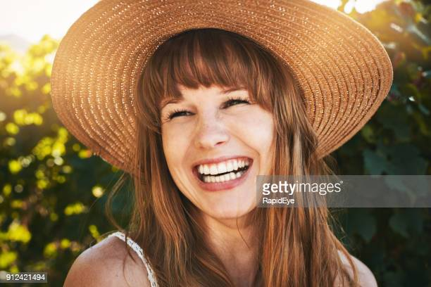 Beautiful young redhead in straw sunhat laughs happily