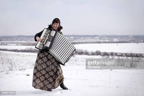 Beautiful young Russian woman playing an accordion