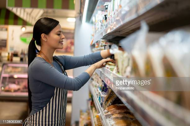 beautiful young sales clerk at supermarket arranging products on shelve smiling - retail place stock pictures, royalty-free photos & images