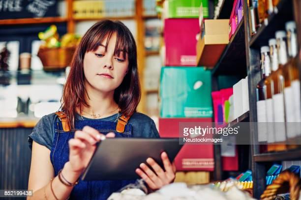 hermosa vendedora joven con tableta digital en delicatessen - lista de chequeo fotografías e imágenes de stock