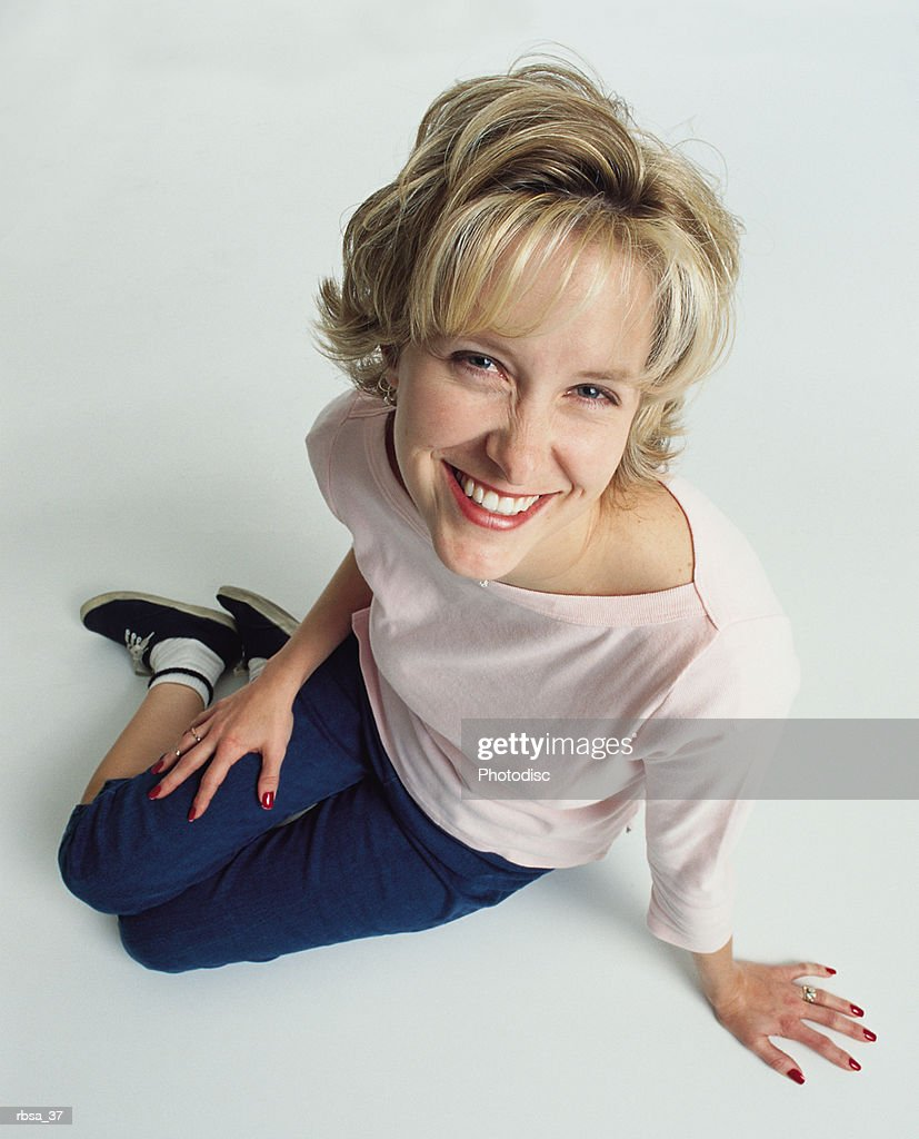 beautiful young slender blonde caucasian adult female wearing jeans and a  pale pink t-shirt and tennis shoes sits on the floor as she leans forward smiling at the camera playfully : Foto de stock