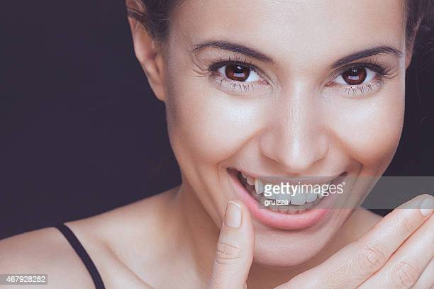 Beautiful young smiling woman covering her smile with hand