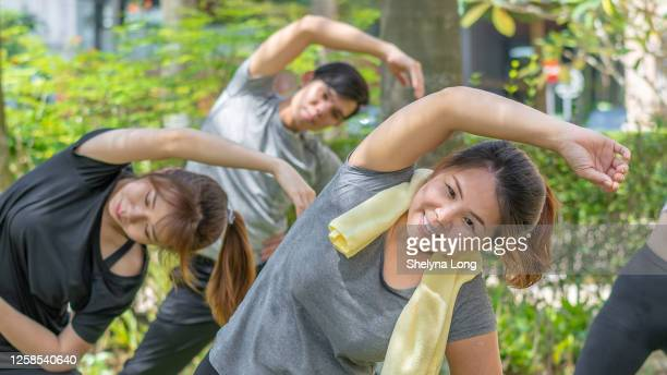 公共の公園で走ってジョギングする前に美しい若いスポーツの女性の運動 - extra long ストックフォトと画像
