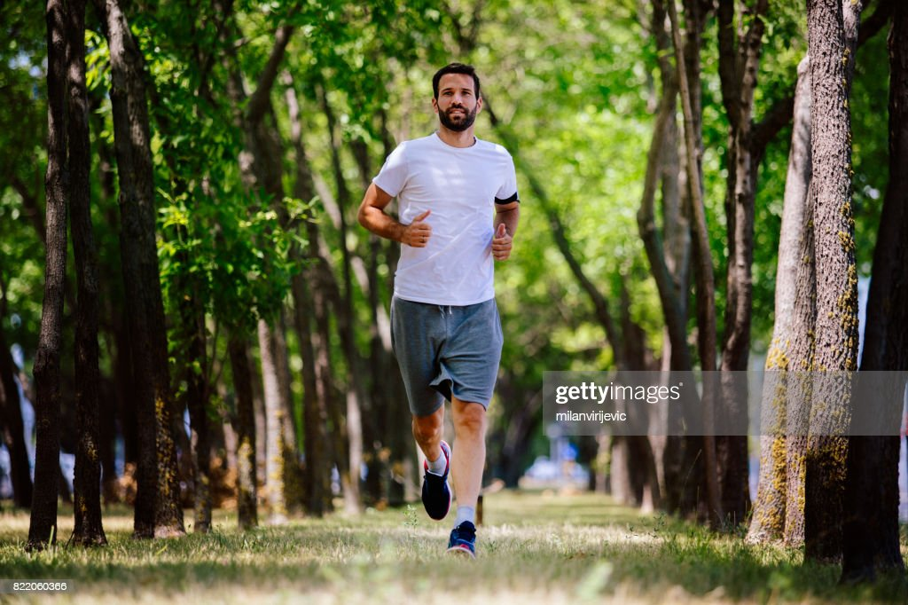 Beautiful young sports man running in nature : Stock Photo