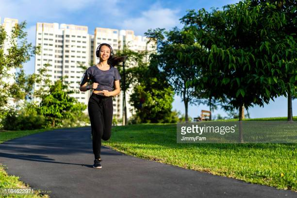 beautiful young sporty asian woman running at public park - filipino woman stock pictures, royalty-free photos & images