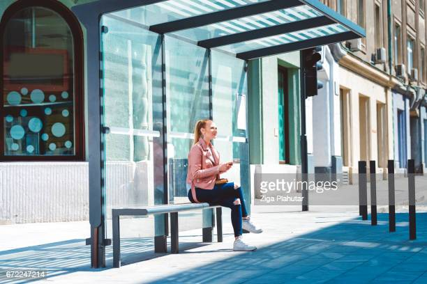 beautiful young student at the glass made bus shelter - estação imagens e fotografias de stock