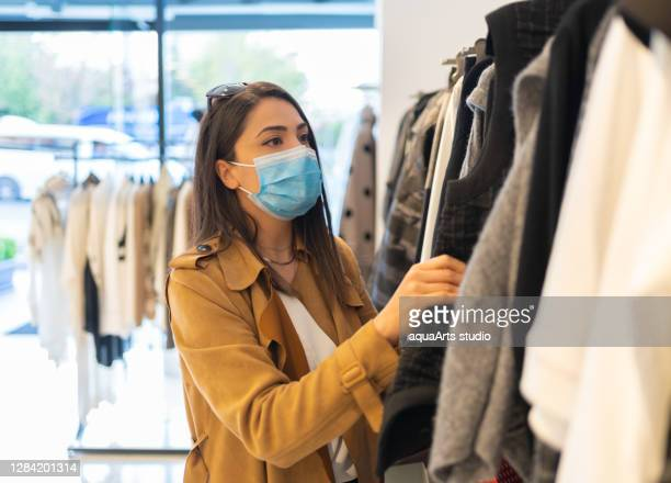 a beautiful young stylish woman with protective face mask is choosing trendy dress in the clothing store during pandemic - shop stock pictures, royalty-free photos & images