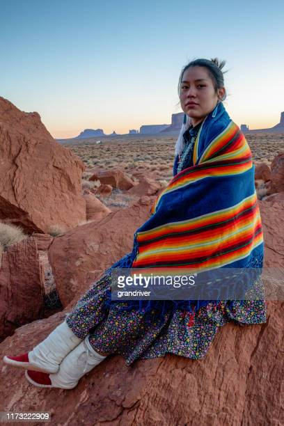 beautiful young teenage native american navajo girl sitting outside at the monument valley tribal park in northern arizona at dawn - navajo hogan stock photos and pictures