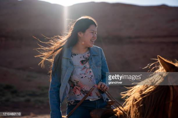 beautiful young teenage navajo native american girl on her horse in the northern arizona monument valley area - native american reservation stock pictures, royalty-free photos & images