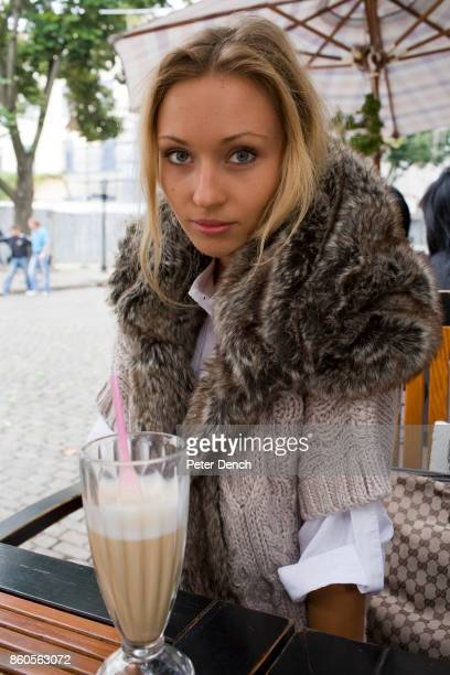 A beautiful young Ukrainian woman sat with a coffee outside one of the many cafes in the centre of Odessa