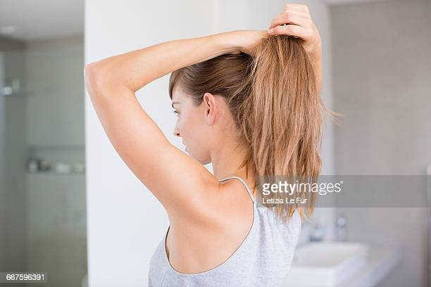 beautiful young woman adjusting her hair in a bathroom - ponytail stock pictures, royalty-free photos & images