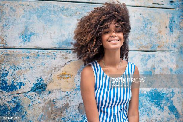 beautiful young woman against weathered blue wall - senza maniche foto e immagini stock