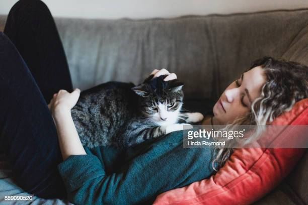 A beautiful young woman and a cat lying down on a sofa