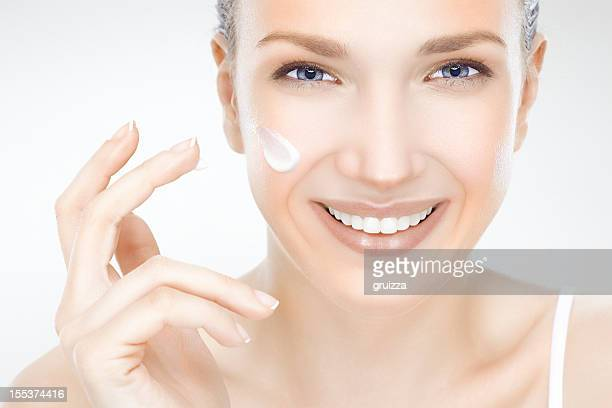 Beautiful, young woman applying cream on her face