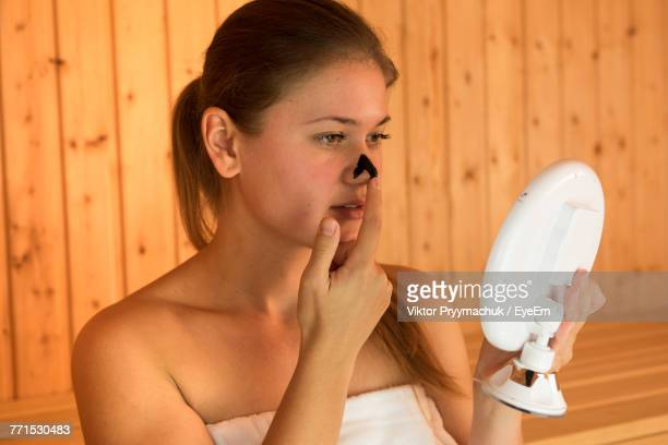 beautiful young woman applying facial mask on face while sitting in sauna - mirror steam stock photos and pictures