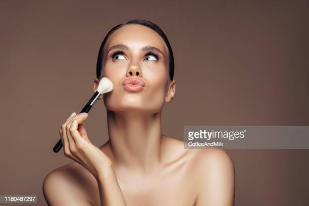 beautiful young woman applying foundation powder - stage make up stock pictures, royalty-free photos & images