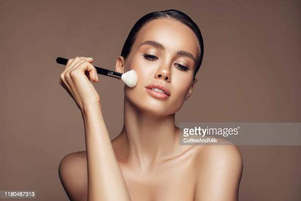 beautiful young woman applying foundation powder - blusher stock pictures, royalty-free photos & images