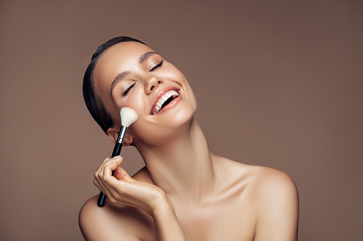 Beautiful young woman applying foundation powder 1180487336