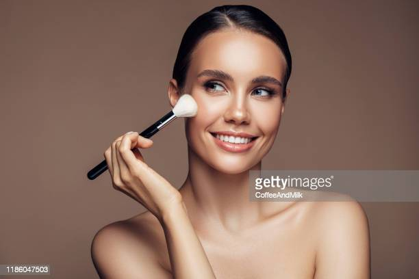 beautiful young woman applying foundation powder - make up stock pictures, royalty-free photos & images
