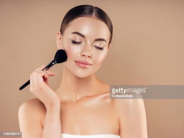 ファンデーションパウダーを適用する美しい若い女性 - メイクアップブラシ ストックフォトと画像