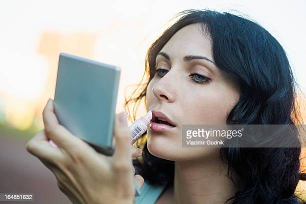 A beautiful young woman applying lipstick using a compact mirror