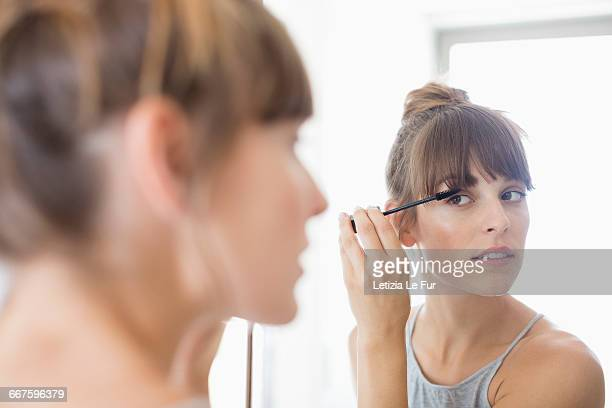 beautiful young woman applying mascara - eye make up stock photos and pictures