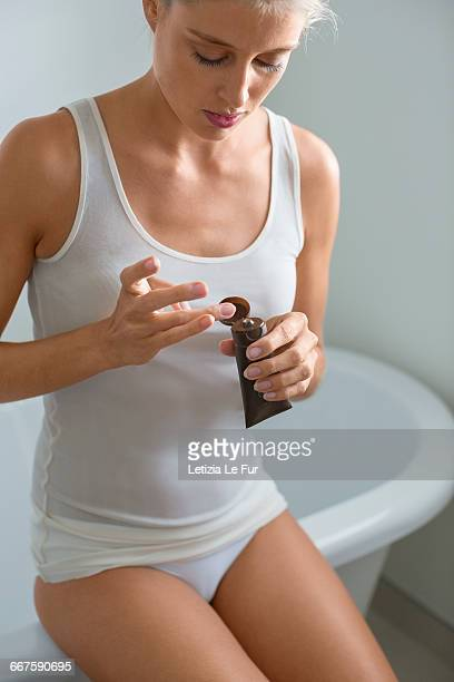 Beautiful young woman applying moisturizer in bathroom