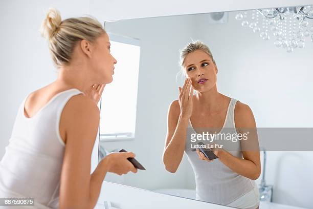 beautiful young woman applying moisturizer on her face in bathroom - una sola mujer joven fotografías e imágenes de stock