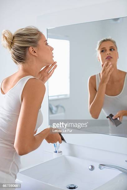 Beautiful young woman applying moisturizer on her face in bathroom