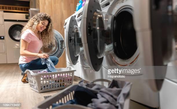 ニコニコしながら彼女の服を洗濯機の読み込み、セルフ サービス ・ ランドリーで美しい若い女性 - セルフサービス ストックフォトと画像