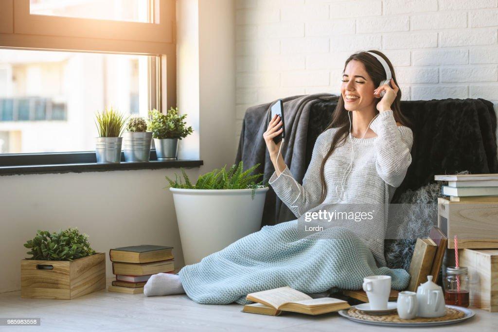 Schöne junge Frau zu Hause hört Musik : Stock-Foto