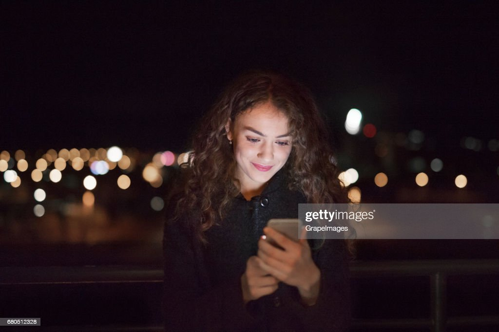 Beautiful young woman at night holding smartphone, texting. : Stock Photo