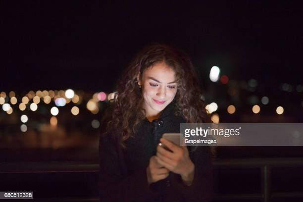 Beautiful young woman at night holding smartphone, texting.