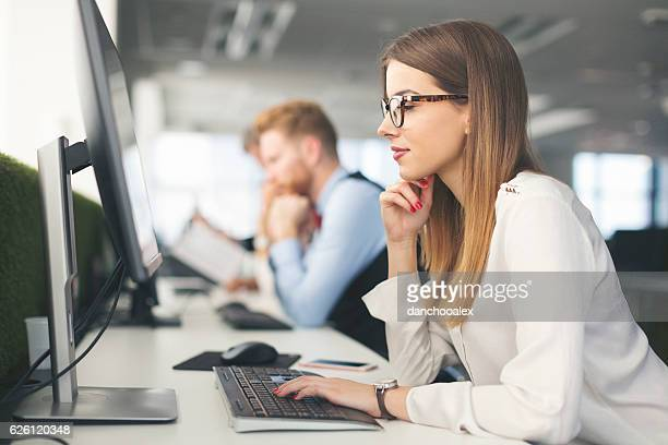 Beautiful young woman at work using computer