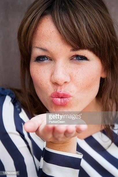 Schöne Junge Frau einen Kuss zuwerfen