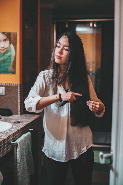 beautiful young woman brushing her long hair in fdomestic bathroom - comb hair stock pictures, royalty-free photos & images