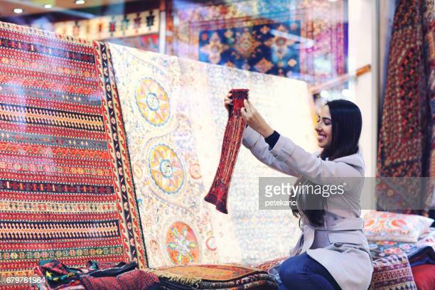 Beautiful young woman buying carpets in Grand Bazaar, Istanbul, Turkey