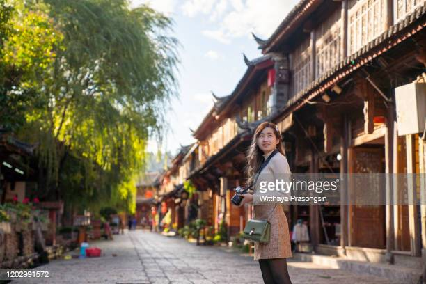 beautiful young woman carrying camera exploring and walking through local city street - local landmark stock pictures, royalty-free photos & images