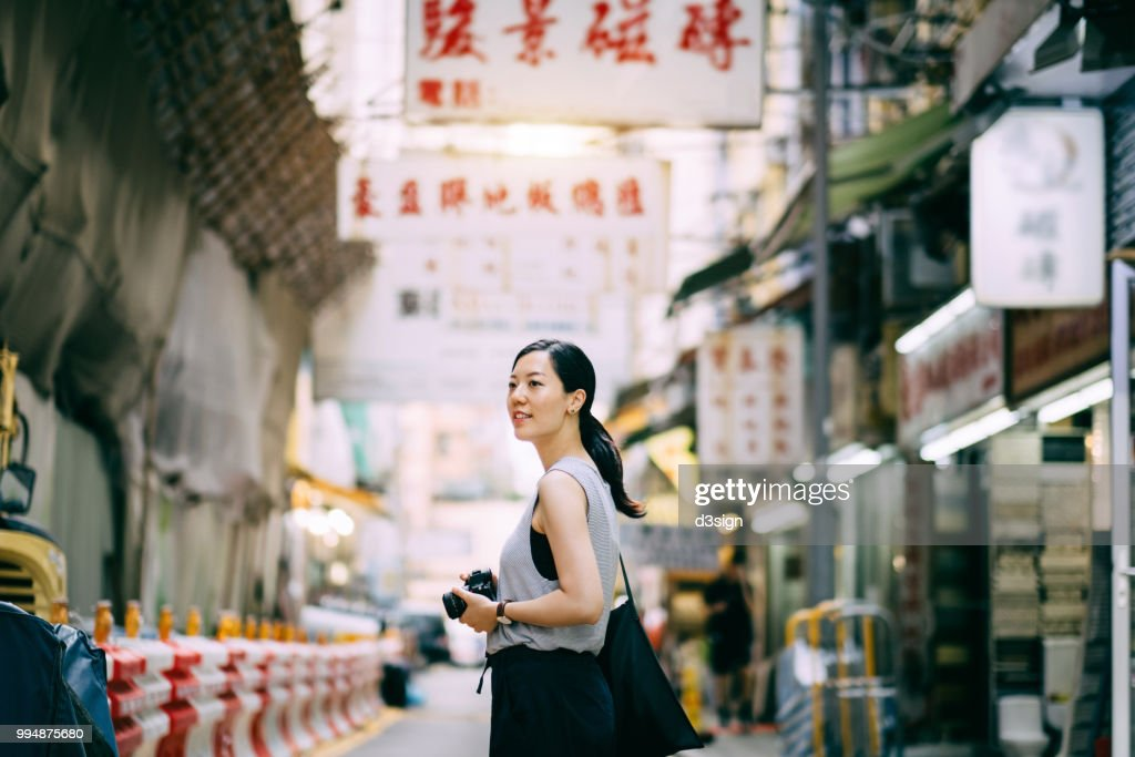 Beautiful young woman carrying camera exploring and walking through local city street : Stock Photo