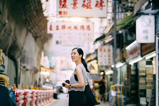 Beautiful young woman carrying camera exploring and walking through local city street - gettyimageskorea