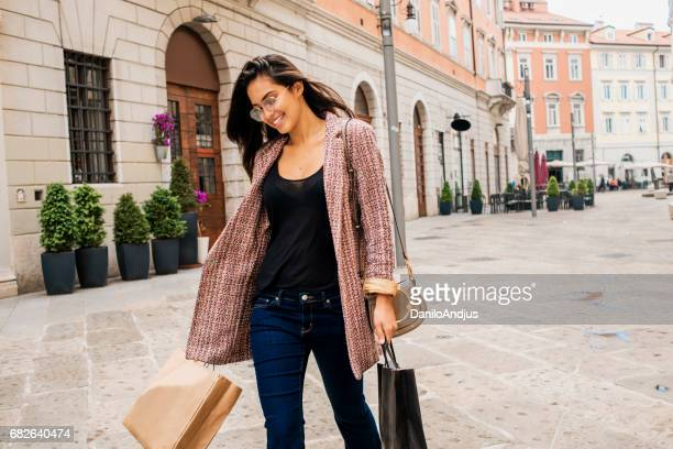 beautiful young woman carrying shopping bags - blazer jacket stock pictures, royalty-free photos & images