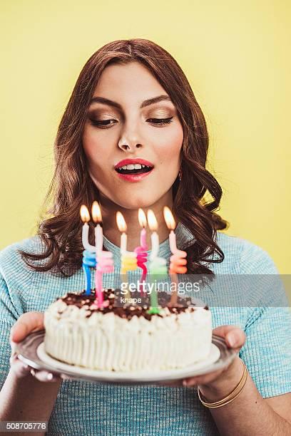 Schöne junge Frau feiern Ihren Geburtstag mit Kuchen
