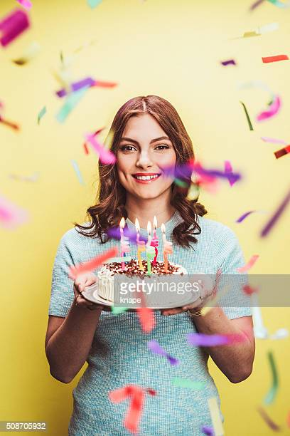 Beautiful young woman celebrating birthday with cake