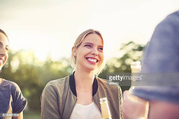 Beautiful young woman chatting with friends on a picnic