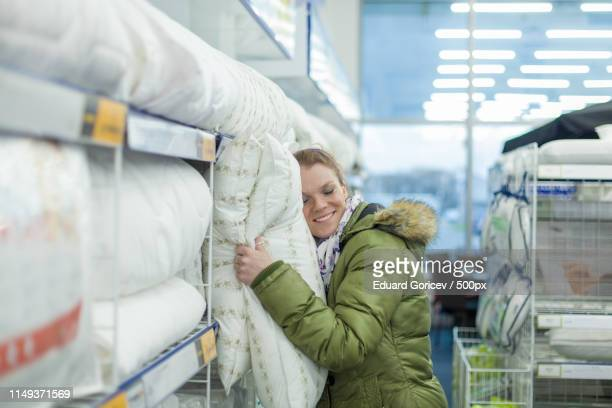 beautiful young woman choose pillows in a furniture store - oreiller geant photos et images de collection