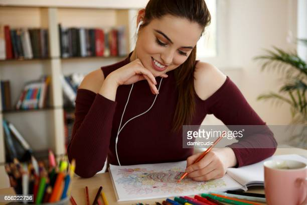 beautiful young woman coloring book and listening music on headphones - colouring stock photos and pictures
